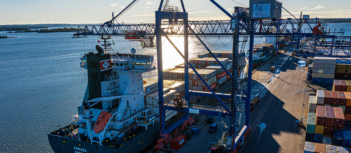 The sun rises in the port of Norrköping with cranes and ships at quay